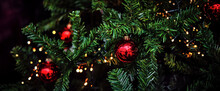 Magical Christmas - X-mas Tree Close-up, Green Pine Branches With Shiny, Traditional Red Ornaments And Ferry Lights. Dark Background, Shallow Depth Of Field, For A Website Banner, Header, Slider
