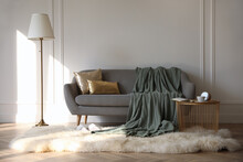 Stylish Room Interior With Comfortable Sofa, Knitted Blanket And Coffee Table Near White Wall