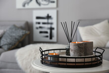 Candles And Aroma Reed Diffuser On White Table Near Grey Sofa, Space For Text