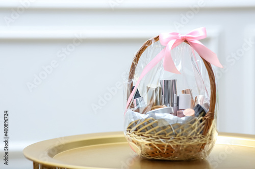 Fotomural Gift set in wicker basket on golden table near white wall