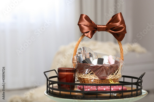 Fotografía Wicker basket full of gifts on table in living room