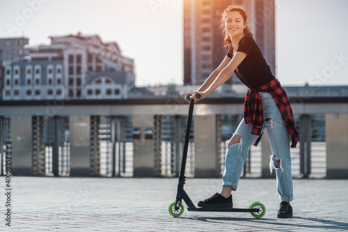 Slika na platnu young teenager in sneaker on modern extreme stunt kick scooter in city