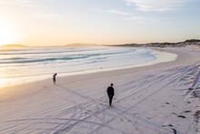 Couple Walking Along Wharton Beach At Sunset.