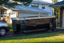 A Small Short Beat Up Black And White Dumpster Containing Wood Debris Located In A Driveway In Front Of A Garage Door
