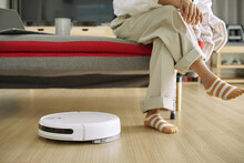 Robotic Vacuum Cleaner Cleaning On Wood Floor In The Living Room While Woman Relaxing On Sofa.