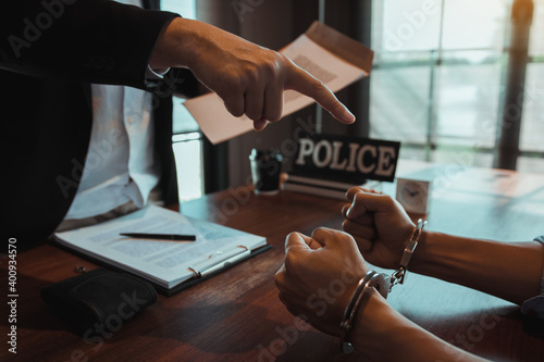 Fotografiet The police officer pointed the handcuffs and held the documents to arrest the accused in a fraud case