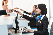 Close Up Caucasian Airline Ground Staff In Black Uniform Receive Passport From Passenger. Concept Of Normal Travel Lifestyle After Ease In Lockdown For Covid-19 Coronavirus Pandemic