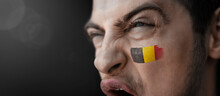 A Screaming Man With The Image Of The Belgium National Flag On His Face