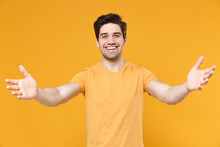 Young Smiling Friendly Unshaved Caucasian Handsome Man 20s Wearing Casual Basic Blank Print Design T-shirt Reach Out Stretch Close Up Hands Camera Isolated On Yellow Color Background Studio Portrait.