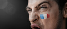 A Screaming Man With The Image Of The France National Flag On His Face