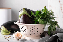 Large Eggplants With Garlic, Parsley And Dill In A White Colander