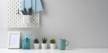 Modern Workspace With Mock Up White Frame, Stationery, Coffee Cup And Houseplant On Well Arranged Desk.