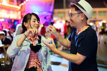 Asian Couple Enjoy Eating On The Street Food At Khao San Road