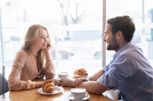 Obraz Positive young couple having breakfast together at cafe, sitting near window and enjoying conversation - fototapety do salonu