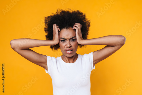 Fotografie, Obraz Displeased upset african american girl frowning and grabbing her head
