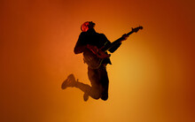 Inspired. Silhouette Of Young Male Guitarist Isolated On Orange Gradient Studio Background In Neon Light. Beautiful Shadow In Action, Performing. Concept Of Human Emotions, Expression, Ad, Music, Art.