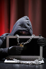 International Hacker In Black Pullover And Black Mask Trying To Hack Government On A Black And Red Background. Cyber Crime . Cyber Security.