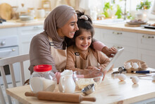 Smiling Muslim Mom And Little Daughter Using Digital Table In Kitchen Together