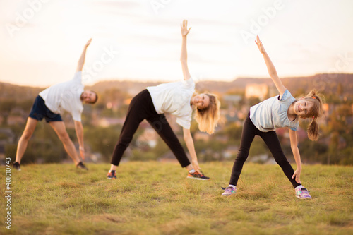 Parents instill sports habits in their child by example, focus on child. Happy sporty family doing stretching exercises, practices yoga outdoor. Mom dad and daughter doing sport exercises