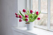 red tulips on old white windowsill