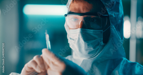 Tela Doctor in protective suit preparing vaccine injection