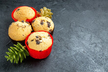 Horizontal View Of Four Delicious Cupcakes And New Year Decorations On Dark Background