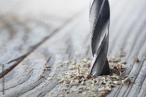 Fototapeta metal drill bit make holes in old wooden plank obraz
