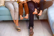 Unrecognizable family's legs on sofa in the living room