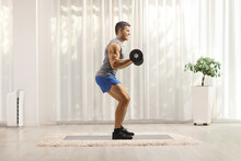 Young Man Bodybuilder Lifting Weights At Home