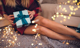Fototapeta Natura - person holding a gift with beautiful legs