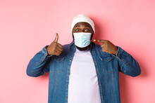 Coronavirus, Lifestyle And Global Pandemic Concept. Young African-american Man Pointing At Face Mask And Showing Thumbs-up, Protect Himself From Covid, Pink Background