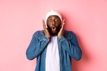 Shocked And Impressed Black Man Staring At Camera With Complete Disbelief, Saying Wow, Standing In Beanie And Hipster Shirt Over Pink Background