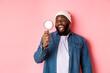 Leinwandbild Motiv Happy african-american man looking through magnifying glass, smiling amazed, standing against pink background