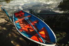 Wooden Colorful Boat With Oars On The Shore Of The Lake In A Bright Summer Day, Image With Retro Tonong
