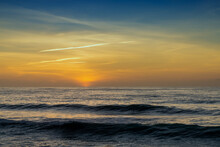 Sunset Over The Ocean With Colorful Sky And Large Waves Rolling In Towards The Coast