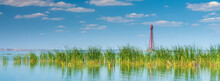 Panoramic View To The Old Red Metal Lighthouse On The River In Summer Day Under Blue Sky With Clouds And Copy Space