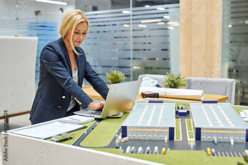 Fotografie, Tablou 3d architect woman working in office with building 3D model, adult female engine