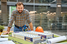 Architect Enjoy Planning The Process Of Building Using Small 3d Model On Table, Look At Camera, Wearing Checkered Casual Shirt