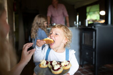 Cute Eager Girl Eating Sweet Pastry At Home