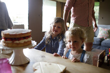 Sisters Looking At Looking At Strawberry Cake On Dining Table