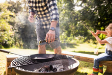 Man Pouring Olive Oil Onto Cast Iron Skillet On Backyard Grill