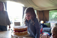 Cute Girl Looking At Strawberry Cake In Yurt Cabin