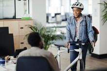 Businesswoman In Helmet With Bicycle Talking To Coworker In Office