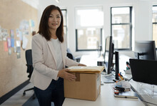 Portrait Smiling Businesswoman Receiving Packages In Office
