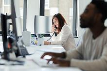 Businesswoman Talking On Telephone At Sunny Office Window