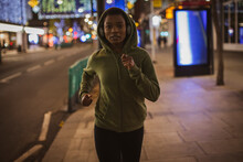 Young Woman In Hoody Running On City Sidewalk At Night