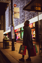 Young Woman With Christmas Shopping Bags On City Sidewalk At Night