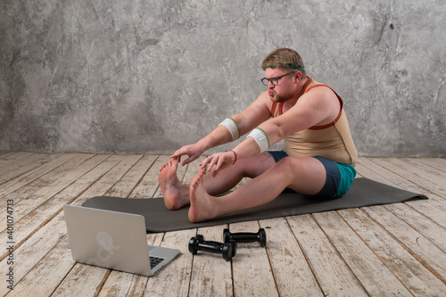 Fototapeta Funny fat man in sportswear doing sports exercises looking into a laptop