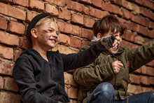 Two Little Street Boys Sit Having Fun Outdoors, They Are Not Sad Despite Their Social Position, Never Give Up. Homeless People