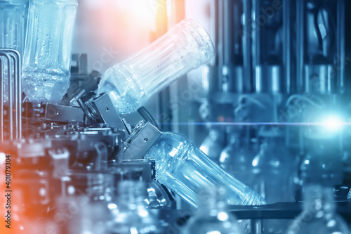 Obraz Abstract industrial background in blue color with filling Plastic bottles inside industrial machine conveyor line in water bottling plant. - fototapety do salonu